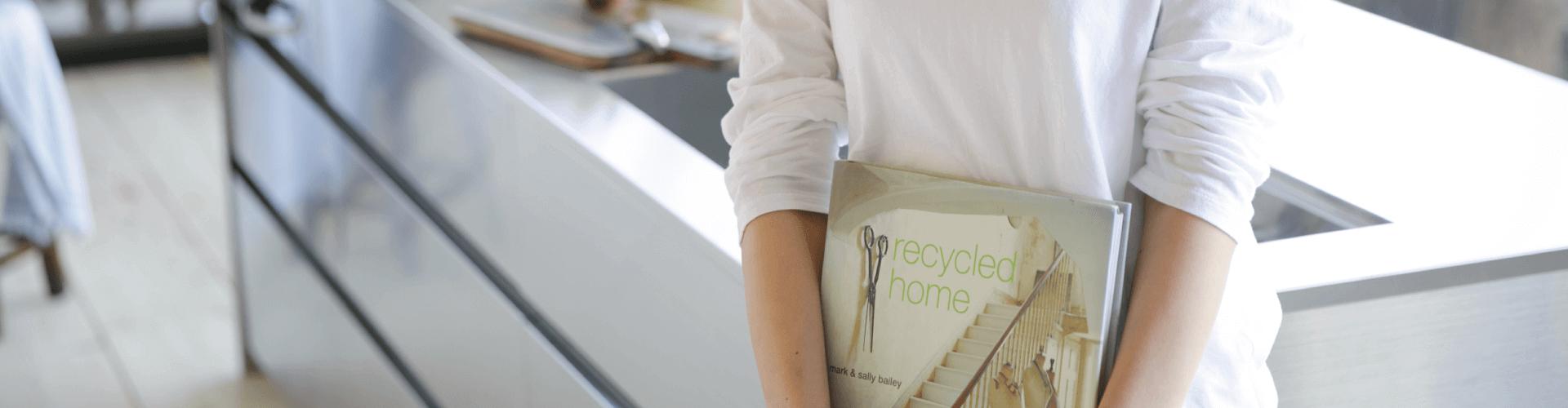 キッチンの前で本を持って立つ女性