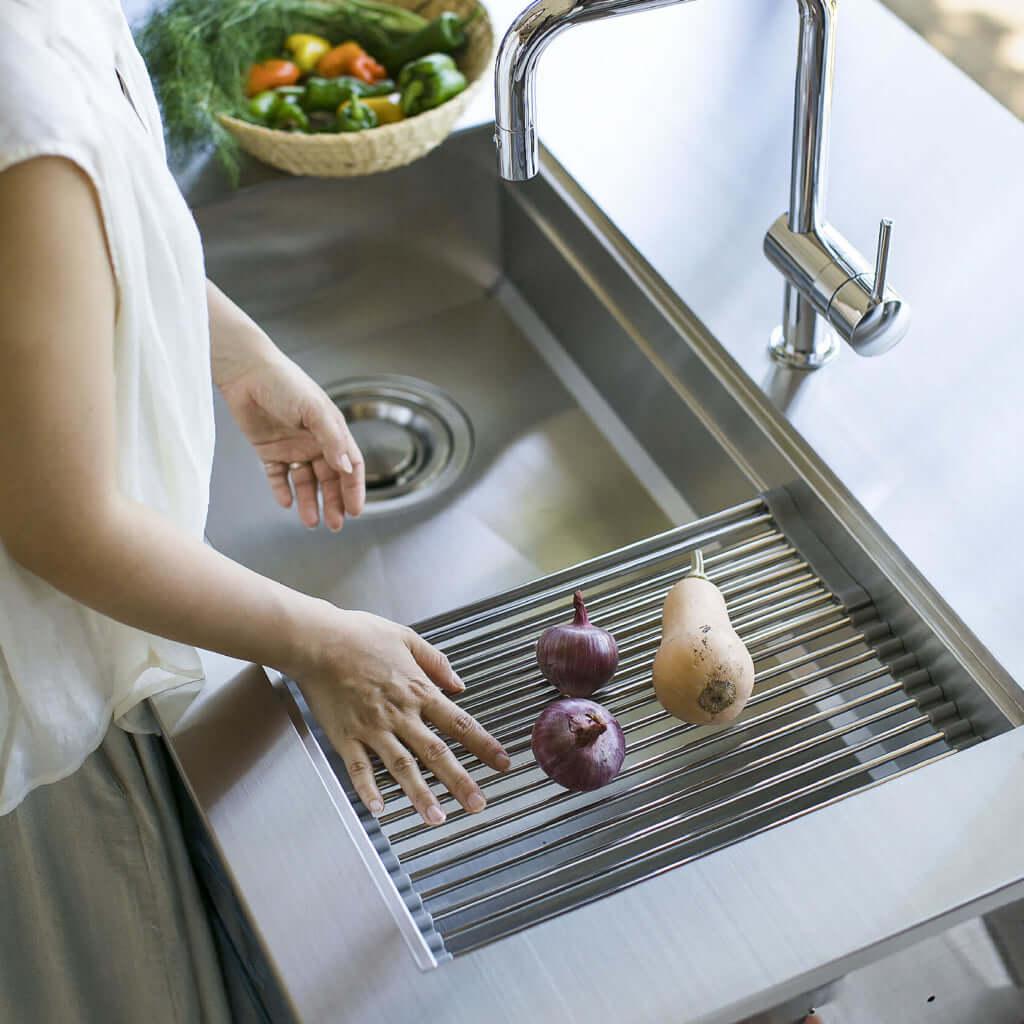 オーダキッチンのシンクで野菜を洗う女性